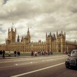 Black Cab Driving Past Houses of Parliament, London
