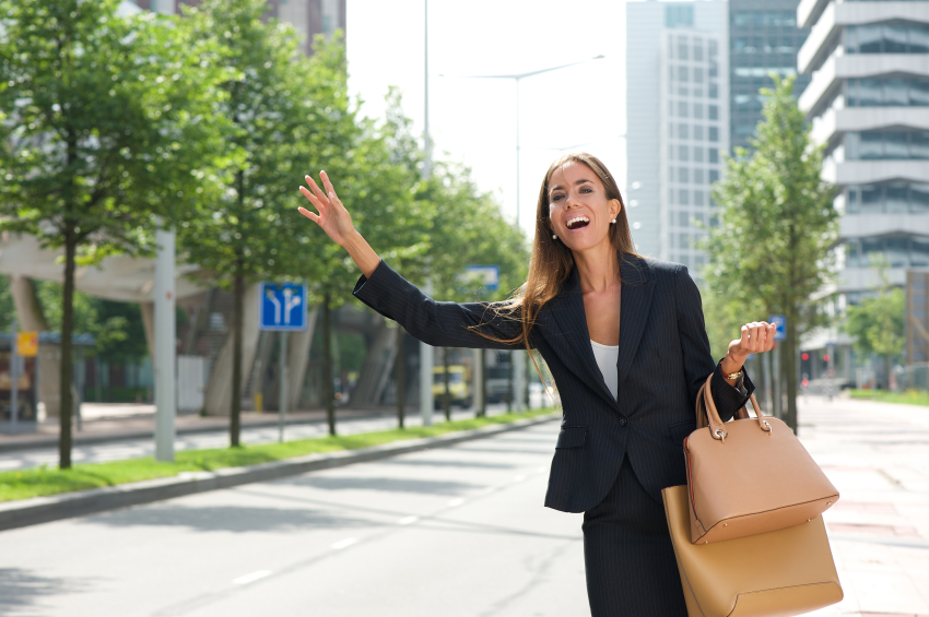 Portrait of a businesswoman with raised arm calling for taxing