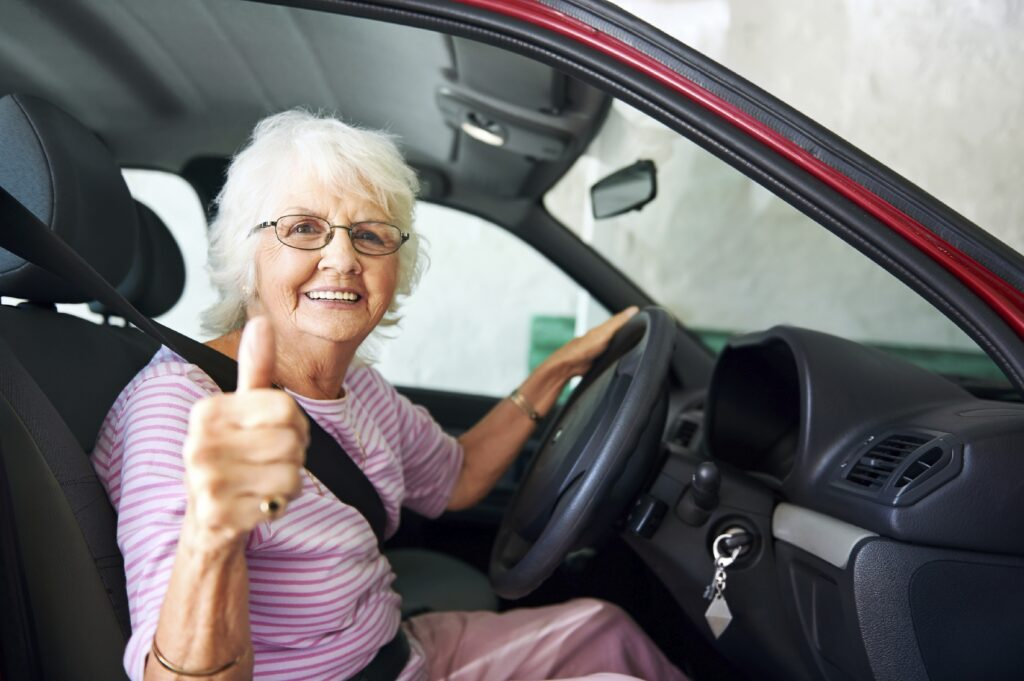 An positive older woman sitting in a car showing a thumbs up